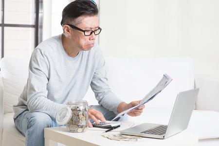 Niepokój 50s dojrzały mężczyzna azjatyckich patrząc na rachunki. Oszczędzanie, emerytury, emeryci koncepcji planowania finansowego.