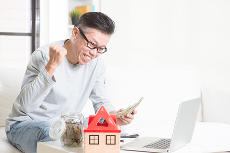 retirees: Portrait of happy 50s mature Asian man counting on money and smiling. Saving, retirement, retirees financial planning concept. Family living lifestyle at home. Stock Photo