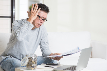 Portrait of 50s mature Asian man having a hard time paying bills. Saving, retirement, retirees financial planning concept. Family living lifestyle at home. Stockfoto