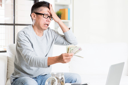 savings problems: Financial crisis concept. Portrait of 50s mature Asian man counting money with sad expression, sitting on sofa at home.