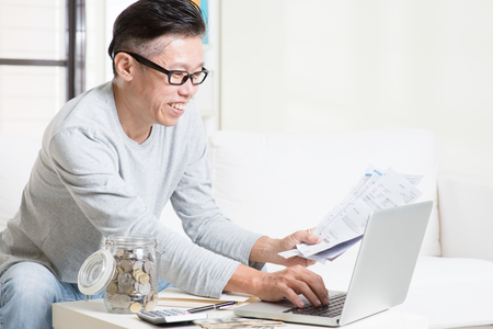 retirees: Portrait of 50s mature Asian man looking at laptop and paying bills online in the living room. Saving, retirement, retirees financial planning concept. Stock Photo