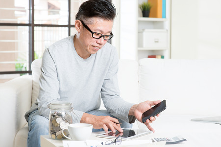 retirees: Mature 50s Asian man doing analysis on his budget, looking on tablet pc and smart phone. Saving, retirement, retirees financial planning concept.