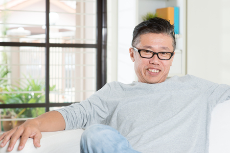 50's: Portrait of happy mature 50s Asian man sitting at home. Senior Chinese male relaxed and seated on sofa indoor. Stock Photo