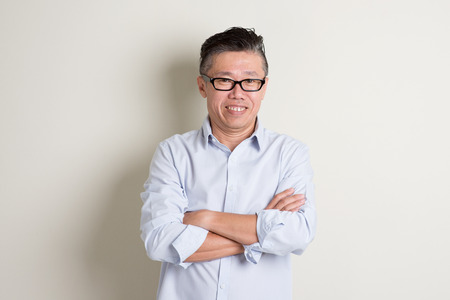 50s: Portrait of confident single mature 50s Asian man in casual business arms crossed and standing over plain background with shadow. Stock Photo