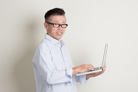 old asian: Portrait of single mature 50s Asian man in casual business using notebook pc and smiling, standing over plain background with shadow. Chinese senior male people.