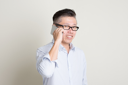 50s: Portrait of single mature 50s Asian man in casual business making a call using smartphone and smiling, standing over plain background with shadow. Chinese senior male people.