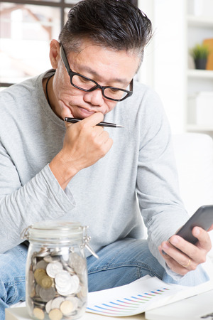 cashflow: Mature 50s Asian man doing analysis on his financial investment, looking on data chart and smartphone. Saving, retirement, retirees financial planning concept.