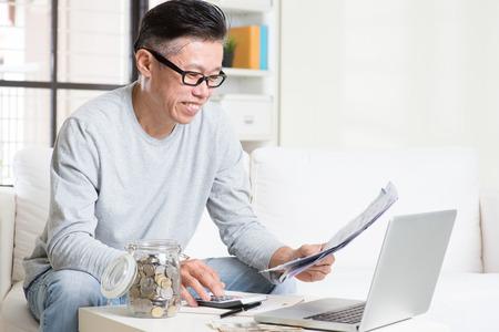 pagando: Retrato de hombre maduro de 50 años asiático que mira el proyecto de ley y un ordenador portátil en la sala de estar. Ahorro, jubilación, jubilados concepto de planificación financiera.
