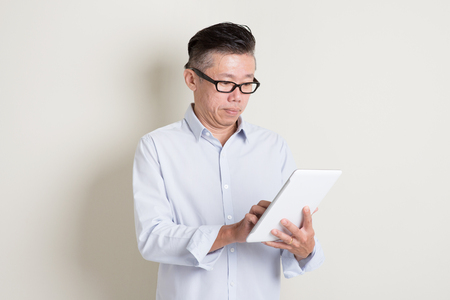 50's: Portrait of single mature 50s Asian man in casual business using digital tablet computer, standing over plain background with shadow. Chinese senior male people. Stock Photo
