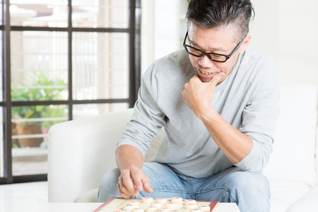 50s: Mature 50s Asian man playing China chess, sitting on couch at home.