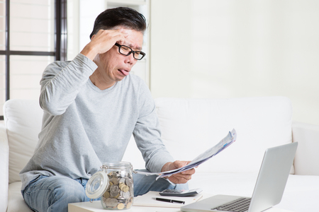 bills: Stressed 50s mature Asian man paying bill at home. Saving, retirement, retirees financial planning concept. Stock Photo