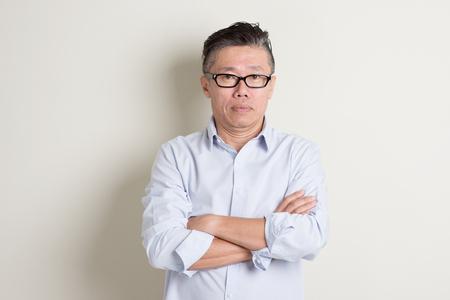 Portret van enkele volwassen jaren '50 Aziatische man in casual zakelijke armen gekruist en permanent over effen achtergrond met schaduw. Stockfoto - 51835747