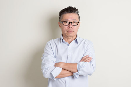 Portrait of single mature 50s Asian man in casual business arms crossed and standing over plain background with shadow.