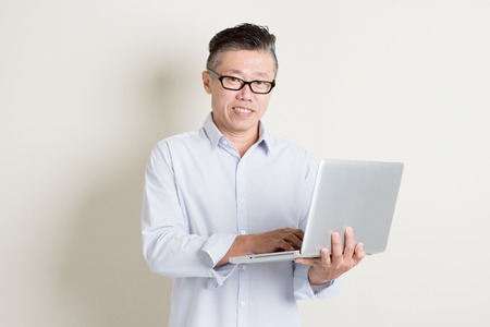 using computer: Portrait of single mature 50s Asian man in casual business using laptop pc and smiling, standing over plain background with shadow. Chinese senior male people.