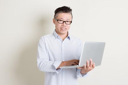 usando computadora: Retrato de 50s maduros solo hombre de Asia en los negocios ocasional que usa la PC portátil y sonriente, de pie sobre fondo llano con la sombra. las personas de sexo masculino de alto rango chinos.