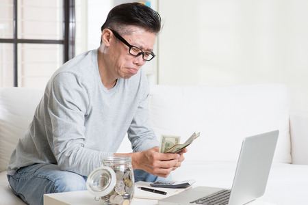 cashflow: Financial problem concept. Portrait of 50s mature Asian man counting money with worried expression, sitting on sofa at home. Stock Photo