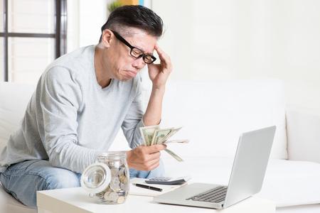 concepto de problema financiero. Retrato de 50 años maduro hombre asiático contar dinero con expresión preocupada, sentado en el sofá en casa. Foto de archivo