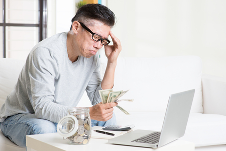 asia people: Financial problem concept. Portrait of 50s mature Asian man counting money with worried expression, sitting on sofa at home. Stock Photo