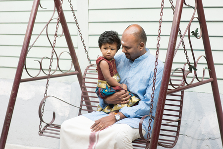 family outdoor: Indian father and daughter sitting on a swing. Traditional India family outdoor portrait. Stock Photo