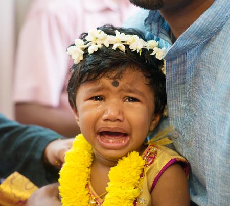 hindues: niña llorando después de eventos karna Veda. Tradicionales hindúes de la India ceremonia de la perforación del oído. India rituales especiales.