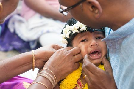 hindues: niña llorando en los eventos karna Veda. Tradicionales hindúes de la India ceremonia de la perforación del oído. India rituales especiales.