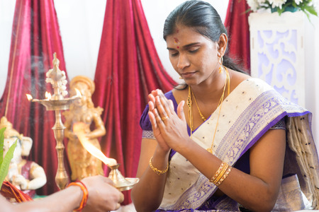 hindus: Woman received prayers from priest. Traditional Indian Hindus ear piercing ceremony. India special rituals.