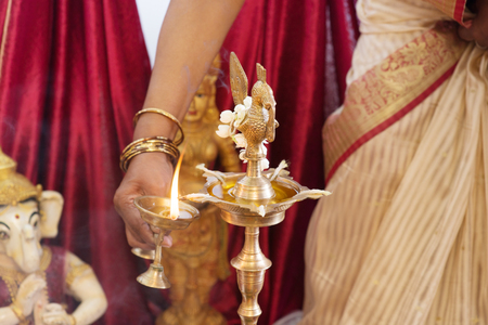 pooja: Woman lighting up the metal diya. Traditional Indian Hindus religious ceremony. Focus on the oil lamp. India special rituals events.