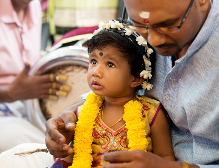 hindus: Baby girl received prayers from the karnvedh events. Traditional Indian Hindus ear piercing ceremony. India special rituals.