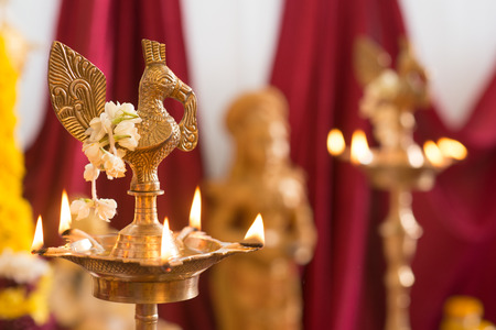 hindus: Metal diya. Traditional Indian Hindus religious ceremony. Focus on the oil lamp. India special rituals events.