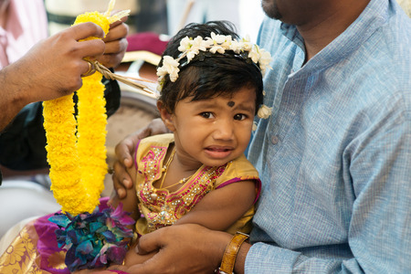 hindus: Baby girl received flower garland from priest. Traditional Indian Hindus ear piercing ceremony. India special rituals.