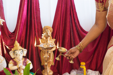 hindus: Woman hand lighting up the metal diya. Traditional Indian Hindus religious ceremony. Focus on the oil lamp. India special rituals events. Stock Photo