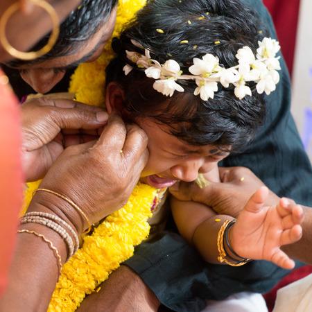 hindues: Bebé que grita durante los eventos karnavedha. Tradicionales hindúes de la India ceremonia de la perforación del oído. India rituales especiales.