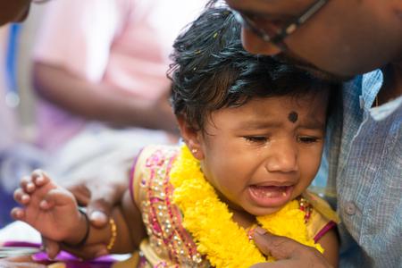 hindues: Padre mimar a su bebé que llora en los eventos karnavedha. Tradicionales hindúes de la India ceremonia de la perforación del oído. India rituales especiales.