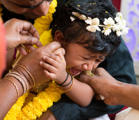 traditional events: Baby girl crying during the karna vedha events. Traditional Indian Hindus ear piercing ceremony. India special rituals. Stock Photo