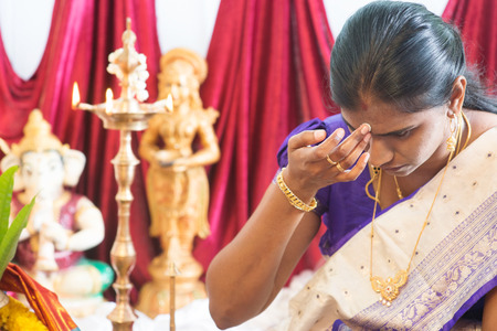 bindi: Hindu woman putting bindi or marking on her forehead during Indian traditional religious rituals, the tradition of Hinduism. Stock Photo