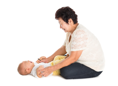 elderly woman: Grandmother comforting crying grandson. Isolated on white background.