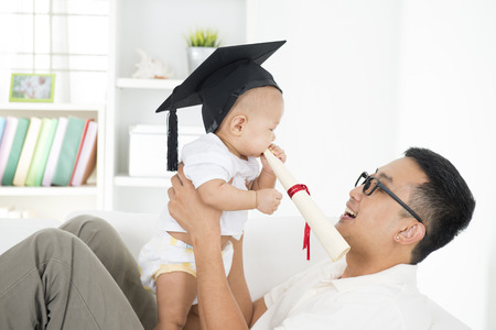 Baby with graduation cap holding certificate with father. Parent and child early education concept. Asian family lifestyle at home.