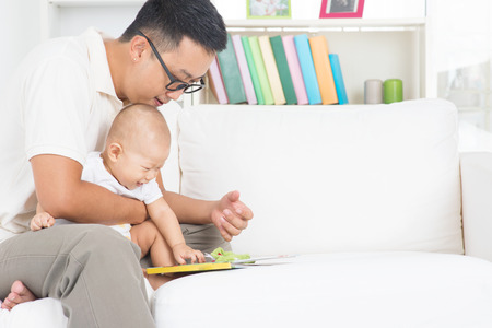 love story: Asian family lifestyle at home. Father and child reading story book on sofa.