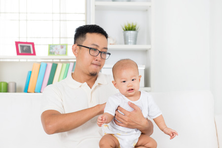 feed: Father burping baby boy after meal, Asian family lifestyle at home.
