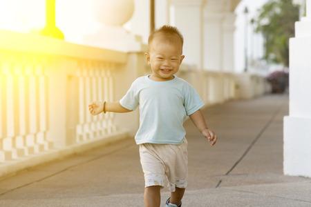 niños chinos: Retrato de chico joven corriendo y sonriendo al aire libre en la puesta del sol. Foto de archivo