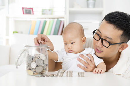 asian coins: Asian family lifestyle at home. Father and baby putting coins into money jar, financial planning concept.