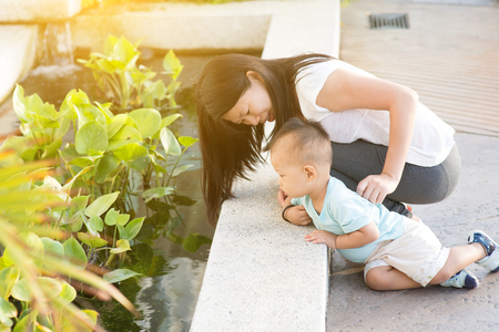 Asian mother and kid having fun time at outdoor in sunset during vacations. photo