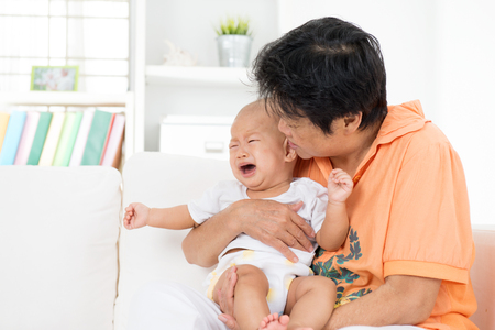 sad old woman: Babysitter comforting crying baby boy at home.
