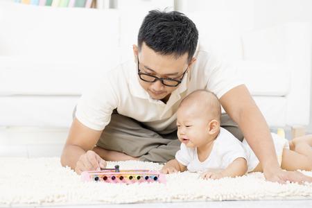 Vader en baby afspelen van muziek instrument. Sound ontwikkeling concept. Aziatische familie lifestyle thuis.