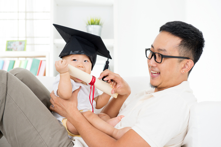 Asian family lifestyle at home. Baby with graduation cap holding certificate with father. Parent and child early education concept.