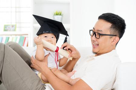 graduado: Forma de vida asiática de la familia en el hogar. Bebé con el casquillo de la graduación que sostiene el certificado con el padre. Padres y concepto de la educación de la primera infancia. Foto de archivo