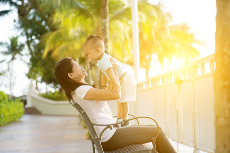 Mother and son having fun at outdoor in sunset during holidays. Banque d'images