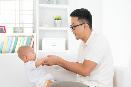 home life: Father and baby boy playing at indoors. Southeast Asian family lifestyle at home.