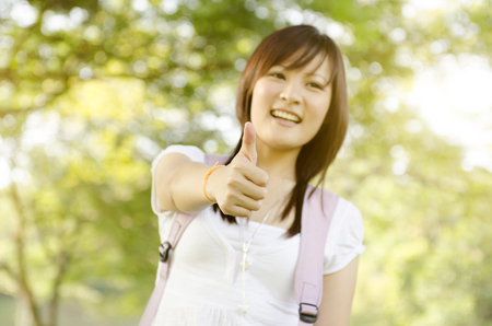 adult education: Young Asian college girl student standing on campus lawn, giving thumb up and smiling.