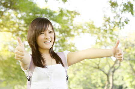 education success: Young Asian university girl student standing on campus lawn, showing thumbs up and smiling. Stock Photo